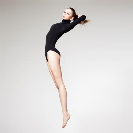 完璧なスリムなボディと長い脚を持つ美しい女性をジャンピング - フィットネスの概念