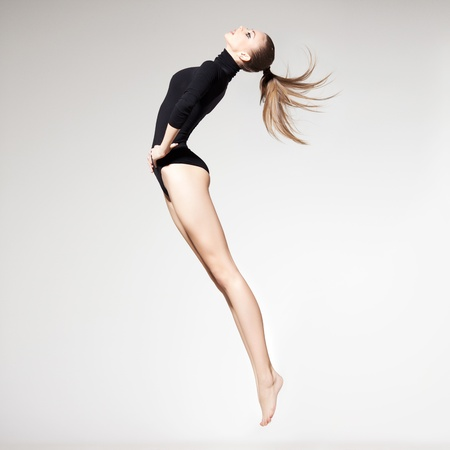 female body: beautiful woman with perfect slim body and long legs jumping - fitness concept
