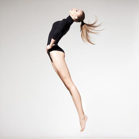 cintura perfecta: hermosa mujer con cuerpo perfecto y delgado saltando las piernas largas - concepto de fitness