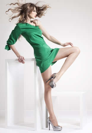 beautiful woman with long sexy legs dressed elegant posing in the studio - full body photo