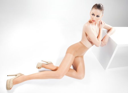 beautiful woman with long sexy legs wearing skin color stockings posing in the studio photo