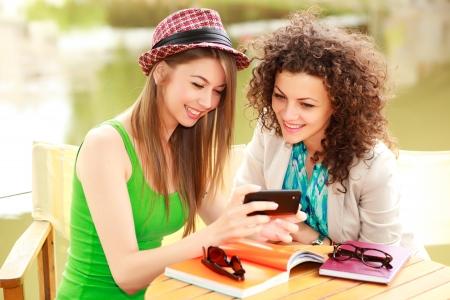 socializando: Dos hermosas mujeres jugando en un tel�fono inteligente y charlando en la terraza junto al r�o Foto de archivo