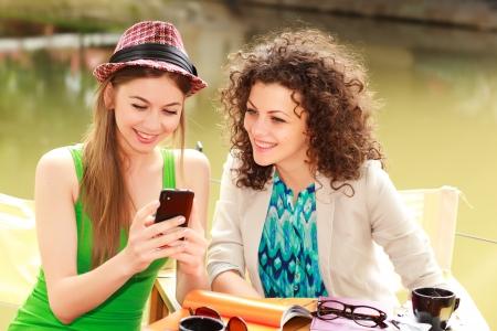 dos personas hablando: Dos hermosas mujeres jugando en un teléfono inteligente y charlando en la terraza junto al río Foto de archivo
