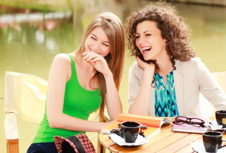 Two beautiful women laughing over a cofee at the river side terrace - vibrat summer colors