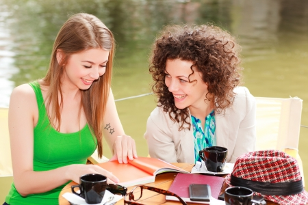 socializing: Two beautiful women chatting over a coffee at the river side terrace Stock Photo