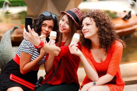 socializando: tres hermosas mujeres fotografiar a sí mismos comiendo helado Foto de archivo