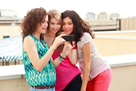 socializando: tres hermosas mujeres buscan en un teléfono inteligente