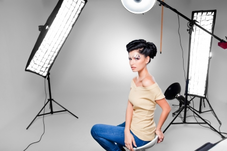 photography studio: young model posing in professionally equipped studio