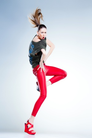 sexy model with slim body dressed in red jumping and screaming in the studio against blueish background photo
