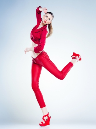 sexy model with slim body dressed in red jumping in the studio against blueish background photo