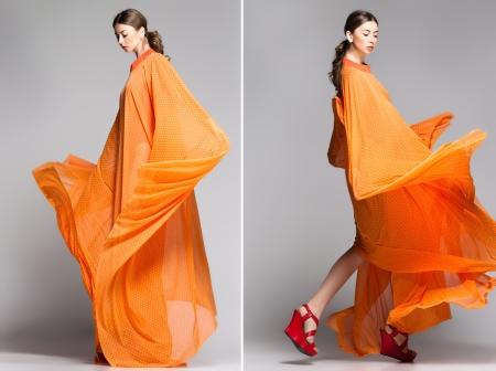 beautiful woman in long orange dress posing dynamic in the studio Standard-Bild