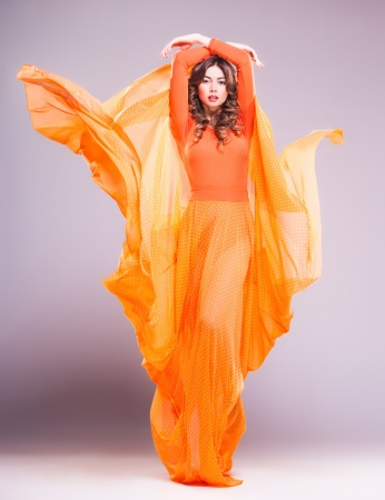 beautiful woman in long orange dress posing dynamic in the studio Zdjęcie Seryjne