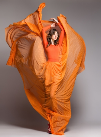 studio model: beautiful woman in long orange dress posing dynamic in the studio Stock Photo