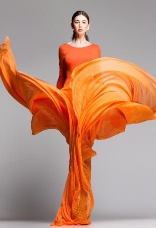 divat: gyönyörű, nő, hosszú narancssárga ruhában pózol dinamikus a stúdióban Stock fotó