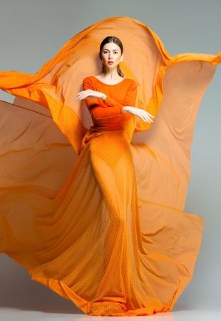 スタジオでダイナミックなポーズ長いオレンジのドレスで美しい女性