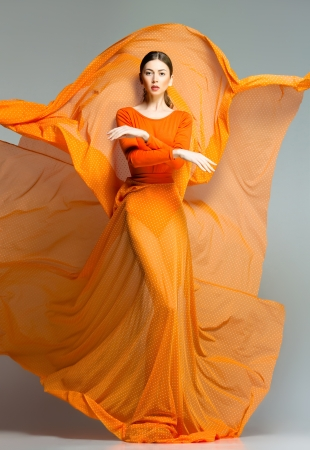 beautiful woman in long orange dress posing dynamic in the studio Stock Photo