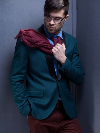 sexy fashion male model dressed elegant - casual posing against wall