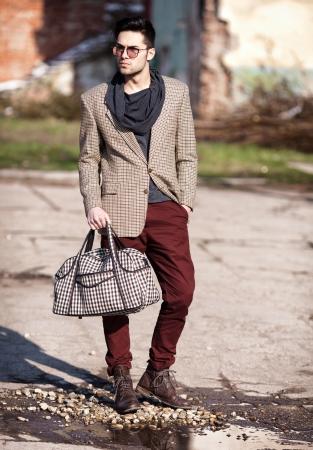 sexy fashion man model dressed elegant holding a bag posing outdoor