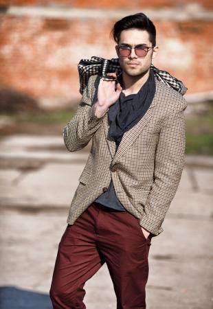 modelo sexy homem moda elegante vestido segurando uma bolsa posando ao ar livre Banco de Imagens
