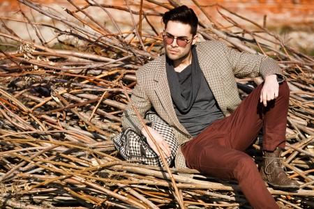 유행: 섹시한 패션 남자 모델은 가방 포즈 야외 들고 우아한 옷을 입고 스톡 콘텐츠