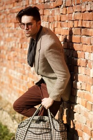 fashion trend: sexy fashion man model dressed elegant holding a bag posing outdoor