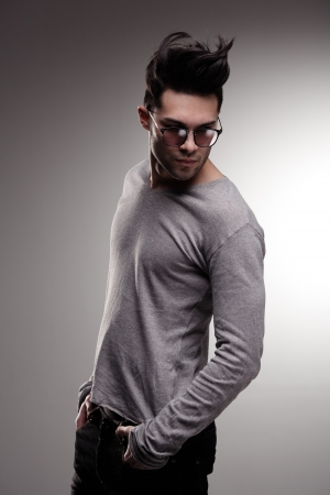 sexy fashion man model dressed casual posing dramatic in the studio - low key photo