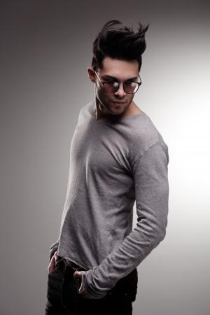 sexy fashion man model dressed casual posing dramatic in the studio - low key