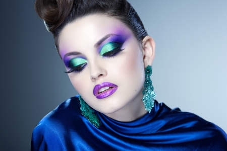 professional blue make-up and hairstyle on beautiful woman face - studio beauty shot photo