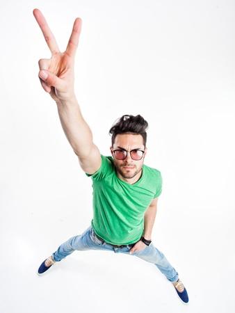 apuesto hombre divertido con gafas inconformista que muestra la victoria y sonriente - fotografías con grandes ángulos Foto de archivo