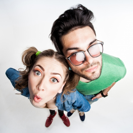 pretty couple dressed casual making funny faces - view from above wide angle shot