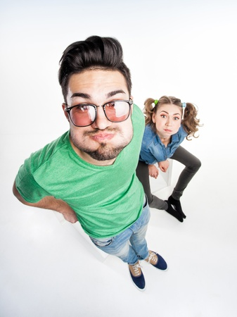 angle views: pretty couple dressed casual making funny faces - view from above wide angle shot