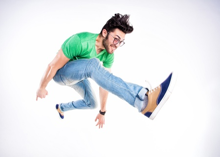 handsome man dressed casual jumping and smiling  - dynamic wide angle shot Standard-Bild