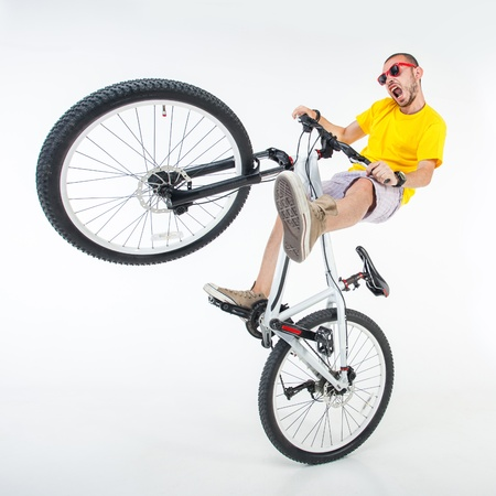 bmx: crazy boy on a dirt jump bike isolated on white - wide studio shot Stock Photo