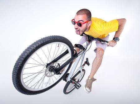 mountain biker: crazy boy on a dirt jump bike making funny faces- wide studio shot