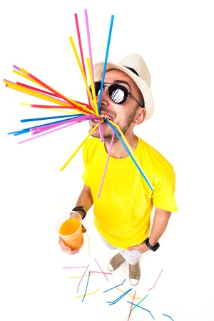 funny man holding a glass of juice wearing sun glasses and yellow t shirt on white  photo
