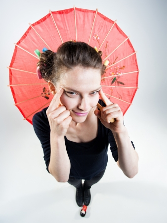 cute girl holding a chinese umbrella and stretching eyes photo