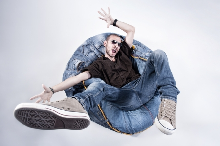 worn jeans: funny crazy man dressed in jeans and sneakers standing on denim beanbag