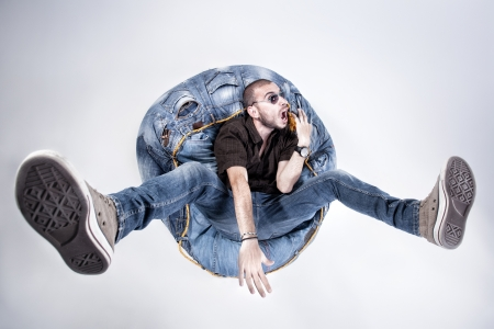 crazy man: funny crazy man dressed in jeans and sneakers standing on denim beanbag