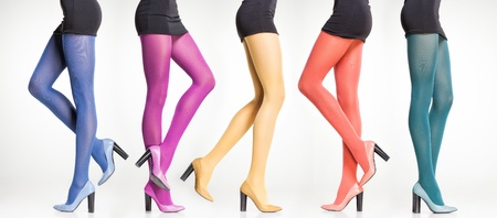 collection of colorful stockings on woman legs isolated on grey