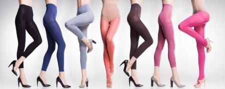 verzameling van kleurrijke panty's en kousen op sexy vrouw benen geïsoleerd op grijs