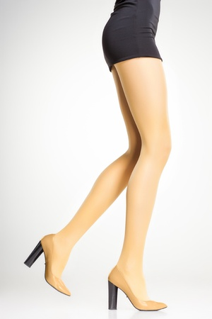 yellow stockings on sexy woman legs isolated on grey