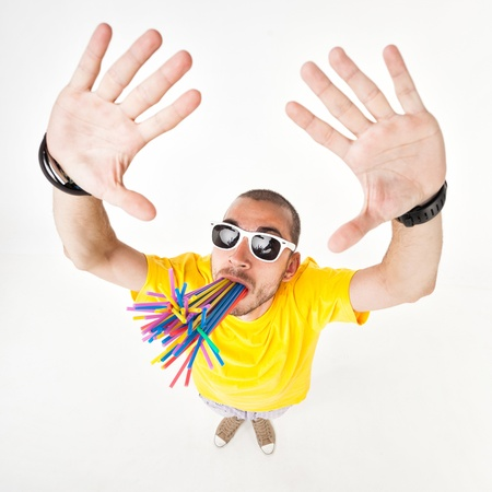 funny man with juice straws in his mouth wearing sun glasses and yellow t shirt photo