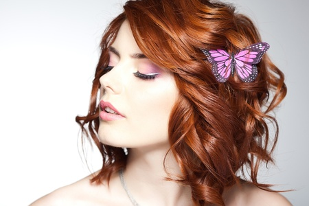 long dark hair: pretty woman with a butterfly in her hair - beauty shot