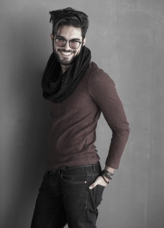 sexy fashion man model dressed casual smiling against wall photo