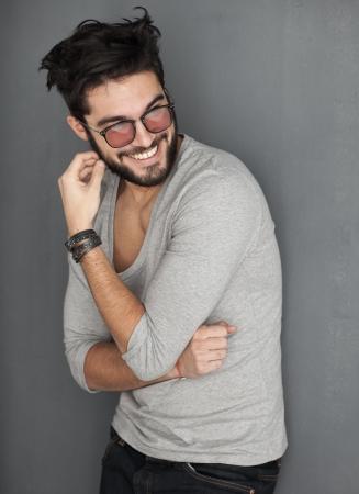 mode: sexig man med skägg klädd avslappnade leende mot väggen