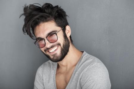 cabello negro: hombre atractivo con barba sonriendo grande contra la pared