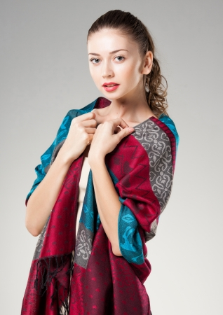 scarves: beautiful woman wearing colorful kashmir scarf isolated on grey