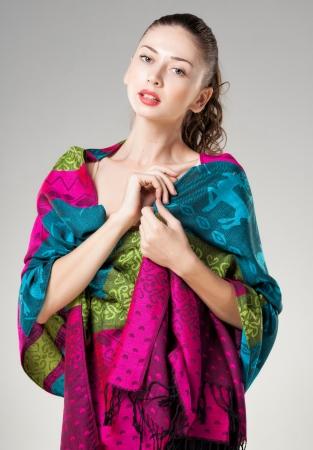 sciarpe: bella donna che indossa colorato sciarpa kashmir isolato su grigio Archivio Fotografico