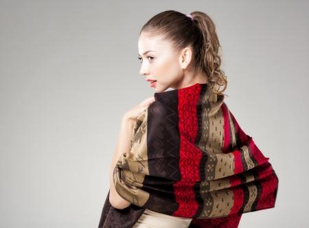 sciarpe: bella donna che indossa colorato sciarpa kashmir isolata sul grigio - paesaggio, copia-spazio