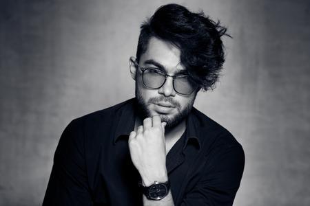 hair man: mod�le sexy de mode homme v�tu de porter des lunettes occasionnels posant dramatique contre le mur de grunge